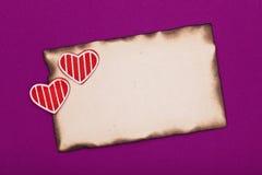 Papel quemado y dos corazones Fotografía de archivo libre de regalías