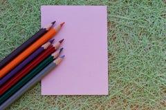 Papel rosado en blanco y lápices coloridos Fotografía de archivo libre de regalías