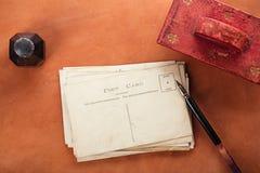 Papel secante de cuero rojo de la tinta del vintage con las postales retras fotografía de archivo