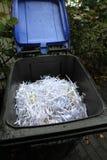 Papel Shredded após shredding em um escaninho azul imagens de stock