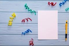 Papel vazio branco e pena amarela com fitas coloridas ao redor Imagem de Stock