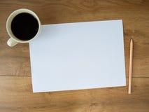 Papel vazio com copo e lápis de café no fundo de madeira Foto de Stock Royalty Free