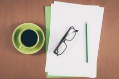 Papel vazio com materiais de escritório com o lápis com vidros e xícara de café Foto de Stock
