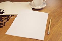 Papel vazio com um caderno com uma xícara de café Fotografia de Stock Royalty Free