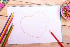 Papel vazio, lápis coloridos e doces sortidos na tabela de madeira foto de stock