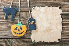 Papel velho para felicitações com Dia das Bruxas e o biscoito caseiro Imagem de Stock