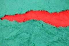 Papel verde rasgado com papel vermelho para dentro Fotografia de Stock Royalty Free