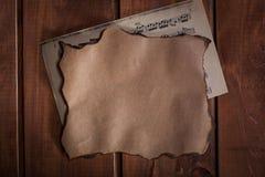 Papel viejo y un blanc con las notas musicales sobre fondo de madera Foto de archivo