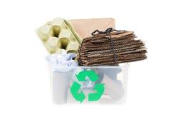 Papel y cartulina en una papelera de reciclaje en el fondo blanco Foto de archivo libre de regalías