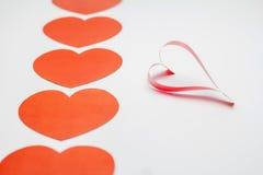 Papel y cinta formados como corazones en el fondo blanco, tarjeta del día de San Valentín Foto de archivo