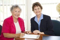 Papeleo de firma de la mujer mayor Imagen de archivo libre de regalías