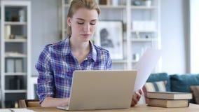 Papeleo, mujer joven que mecanografía en el ordenador portátil y que trabaja en documentos metrajes