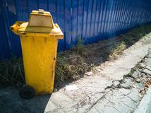 Papelera de reciclaje amarilla en el piso y la pared azul Fotografía de archivo