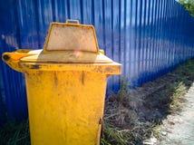 Papelera de reciclaje amarilla en el piso y la pared azul Fotos de archivo libres de regalías