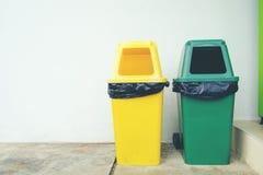 Papelera de reciclaje plástica amarilla y verde de la basura en el piso y la pizca Imagenes de archivo