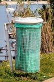 Papelera de reciclaje verde en la hierba fotografía de archivo