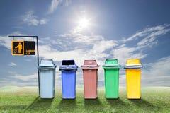 Papeleras de reciclaje en el fondo de la hierba verde y del cielo, concepto de la ecología Fotografía de archivo libre de regalías