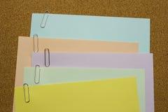Papeles con el clip de papel atado en el tablero marrón Fotos de archivo libres de regalías