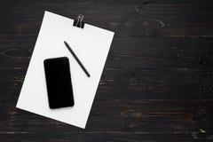 Papeles con la pluma y celular en fondo de madera Imagen de archivo libre de regalías