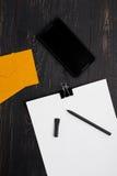 Papeles con la pluma y los sobres y celular en fondo de madera Fotografía de archivo