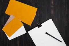 Papeles con la pluma y sobres en fondo de madera Imagen de archivo libre de regalías