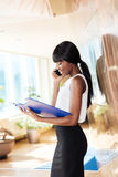 Papeles de la lectura de la empresaria y el hablar en el teléfono imágenes de archivo libres de regalías