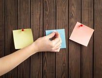 papeles de nota con la mano Foto de archivo libre de regalías