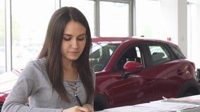 Papeles de relleno del conductor femenino atractivo joven en la concesión de coche almacen de video