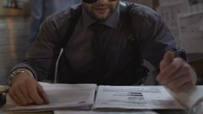 Papeles de repaso del caso del policía fresco, buscando las pistas, trabajando en oficina almacen de metraje de vídeo