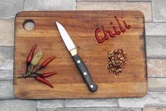 Papeles del chile caliente en una tarjeta de corte foto de archivo