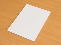 Papeles en blanco en la tabla de madera de la oficina Fotografía de archivo libre de regalías