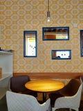 Papeles pintados y espejos amarillos en interior del café foto de archivo