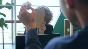Papeles que lanzan sonrientes jovenes de la mujer de negocios y diversión el tener con los colegas en la oficina 4K almacen de metraje de vídeo