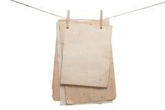 Papeles viejos que cuelgan en la cuerda con las pinzas Foto de archivo libre de regalías