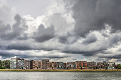Papendrecht waterfront under a stormy sky. View across the Merwede river towards the waterfront of the town of Papendrecht, with modern appartment buildings royalty free stock photography