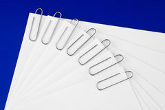 Paper. A set of papers with paper clips, on a blue background, for office design royalty free stock photos