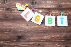 Paper with abbreviation LGBT. And heart hanging on brown wooden background royalty free stock photography