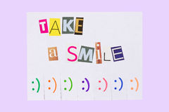 A paper ad with the phrase: Take a Smile and with smile signs ready to be tore off Stock Images