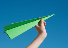 Paper aeroplane. Green travel concept with a hand holding a green paper aeroplane against a blue sky Royalty Free Stock Image