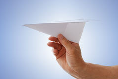 Paper aircraft is launched from hand. stock photos
