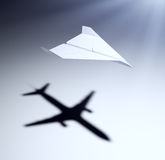 Paper airplane with big aspirations. Paper airplane casting a shadow of a jetliner - vision and aspirations concept illustration Stock Image
