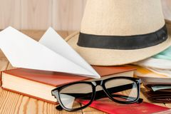 Paper airplane, book, glasses and hat for travel. Close-up royalty free stock photos