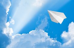 Paper airplane flying in the sky. Among the clouds Stock Photography