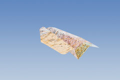 Paper airplane - geographical map. Paper airplane made from geographical map flying royalty free stock photos