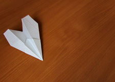 Paper airplane. Made of a tetradic sheet, lies on the wooden table Royalty Free Stock Photography