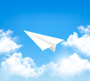 Paper airplane in the sky with clouds. Stock Image