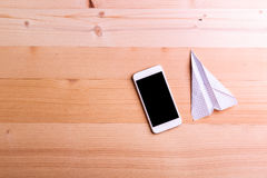 Paper airplane, smart phone against wooden background, copy spac. Paper airplane and smart phone against wooden background, empty copy space stock photos