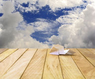 Paper airplane on a wooden platform. Stock Photo