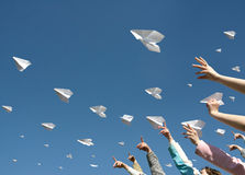 Paper airplanes. The hands of children throw upwards messages in the manner of paper airplanes