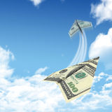 Paper airplanes made of hundred dollar bills. Sky and clouds in the background Royalty Free Stock Photo
